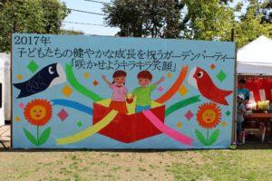 大きな立て看板:子供たちの健やかな成長を祝うガーデンパーティー「咲かせようキラキラ笑顔」